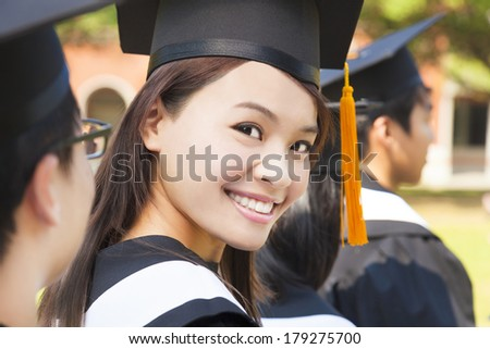 smiling woman standing out from a graduation group - stock photo
