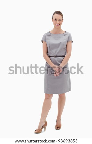 Smiling woman standing up and holding her hands against white background - stock photo