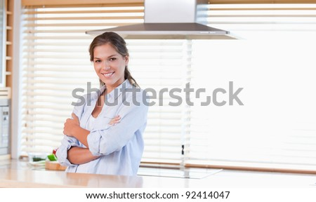 Smiling woman standing up in her kitchen - stock photo
