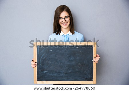 Smiling woman standing with billboard over gray background. Wearing in blue shirt and glasses. Looking at camera - stock photo