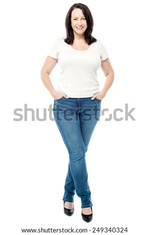 Smiling woman standing with hands in pockets - stock photo