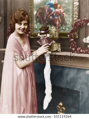 Smiling woman stuffing Christmas stocking - stock photo