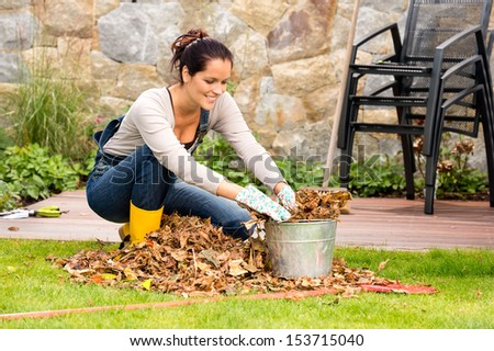 Smiling woman stuffing dry leaves into bucket autumn garden housework - stock photo