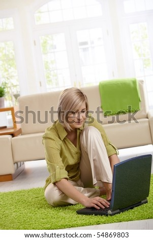 Smiling woman surfing the internet on laptop computer at home. - stock photo