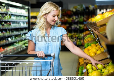 Smiling woman taking lemon in grocery shop - stock photo