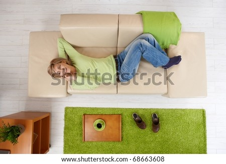 Smiling woman talking on phone,having coffee mug on tray, lying on couch, in overhead view.?