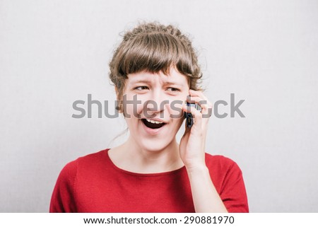 Smiling woman talking on the phone. On a gray background.