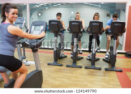 Smiling woman teaching spinning class to four people in gym - stock photo