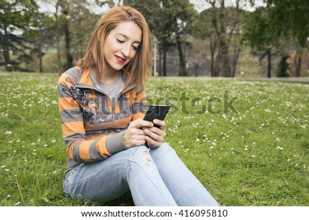 Smiling woman texting on a smart phone, outdoors, sitting on the green grass.