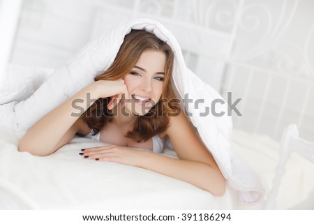 Smiling woman under a duvet in her bedroom. Closeup portrait of a beautiful young woman with red hair and under the blanket. happy good morning - stock photo