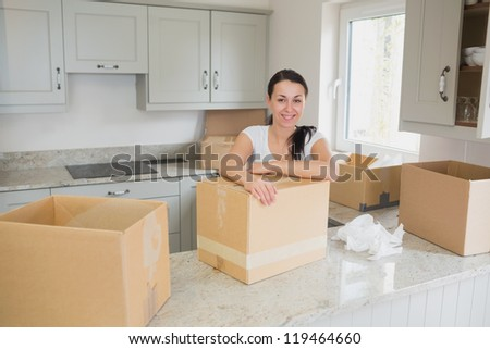 Smiling woman unpacking in kitchen - stock photo