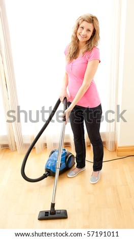 Smiling woman use vacuum cleaner in a living room - stock photo