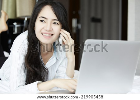 Smiling woman using a laptop and phone while lying on her bed.