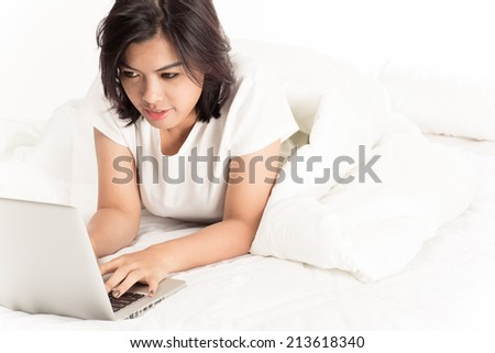 Smiling woman using a laptop while lying on her bed
