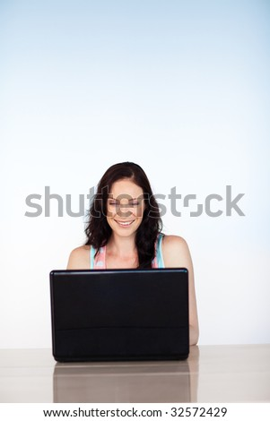 Smiling woman using her laptop at home with copy-space