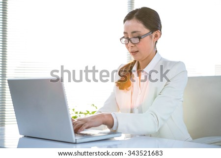 Smiling woman using her laptop at the desk in work