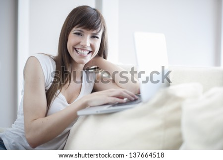 Smiling woman using her laptop sitting on the couch in her home. She is looking at camera and smiling - stock photo