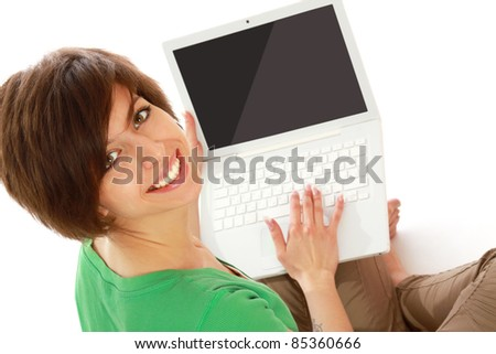 Smiling woman using laptop while sitting on floor isolated - stock photo