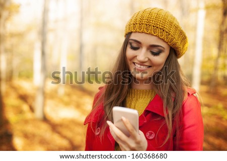 Smiling woman using mobile phone in park during the autumn   - stock photo