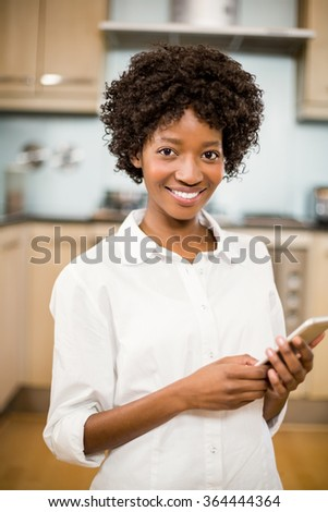 Smiling woman using table smartphone in the kitchen - stock photo