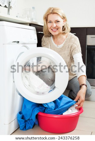 Smiling woman using washing machine at home laundry - stock photo