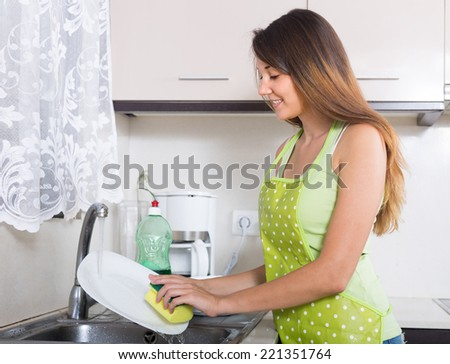 Smiling woman washing plates with sponge in domestic kitchen  - stock photo