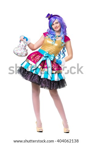 Smiling woman wearing colorful dress and blue wig posing with teapot. Isolated on white