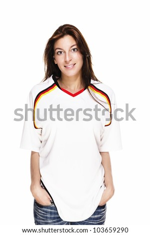 smiling woman wearing football shirt with hands in her pockets on white background - stock photo
