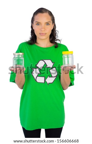 Smiling woman wearing green recycling tshirt holding two glass jars on white background - stock photo