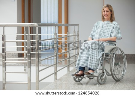 Smiling woman wearing hospital gown sitting in wheelchair in hospital corridor - stock photo