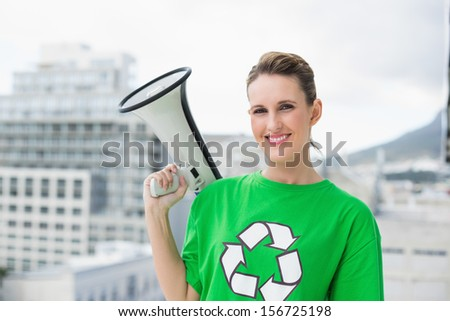 Smiling woman wearing recycling tshirt holding megaphone outside on a bright day - stock photo