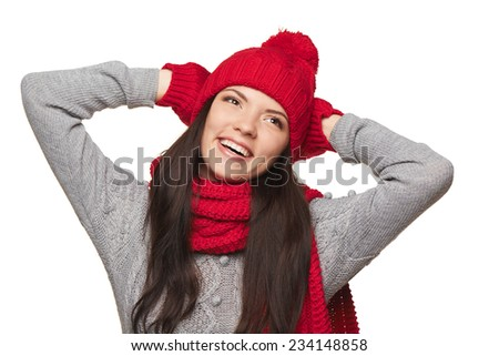 Smiling woman wearing red winter hat, scarf and mittens enjoying with hands over head, over white background