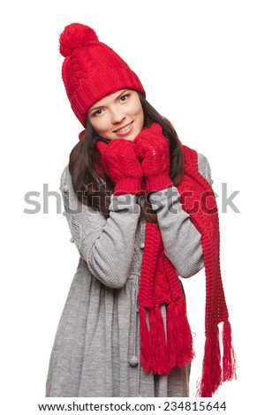 Smiling woman wearing red winter hat, scarf and mittens over white background