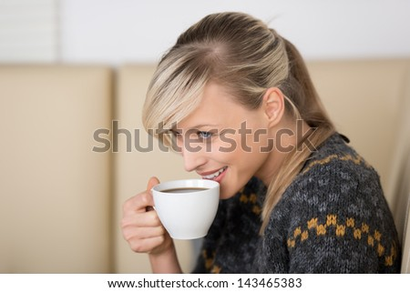 Smiling woman with a freshly brewed cup of espresso coffee in her hand sitting on a comfortable couch, head and shoulders side view portrait