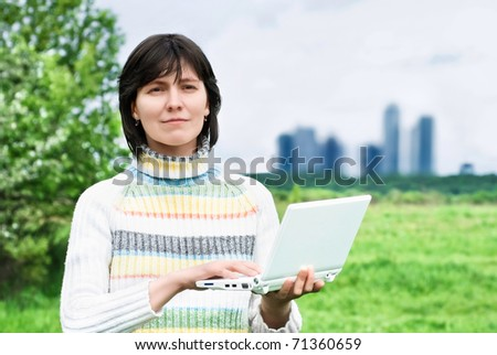 Smiling woman with a laptop on the background of the city buildings