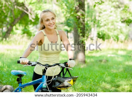 Smiling woman with a mountain bicycle in park