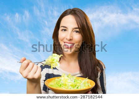 Smiling woman with a salad. Over clouds background