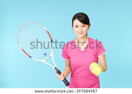 Smiling woman with a tennis racket