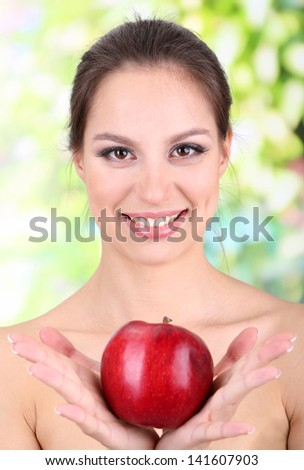 Smiling woman with apple on bright background