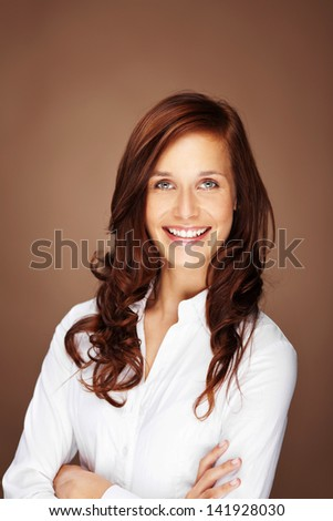 Smiling woman with arm crossed over the brown background
