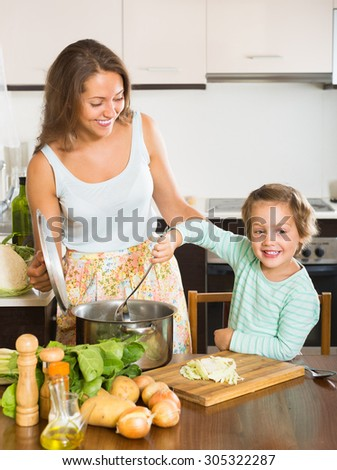 Smiling woman with baby cooking with vegetables at home kitchen