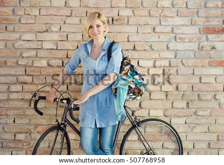 Smiling woman with bicycle front of brick wall.
