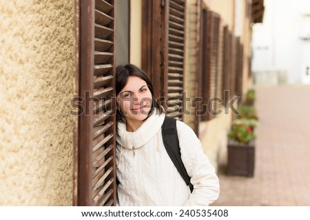 smiling woman with black straps of backpack