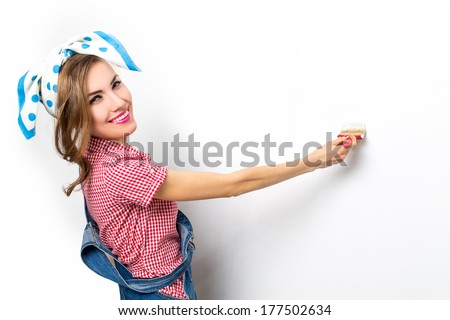 Smiling woman with brush painting wall in her house - stock photo