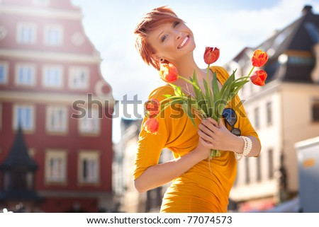 Smiling woman with bunch of flowers - stock photo