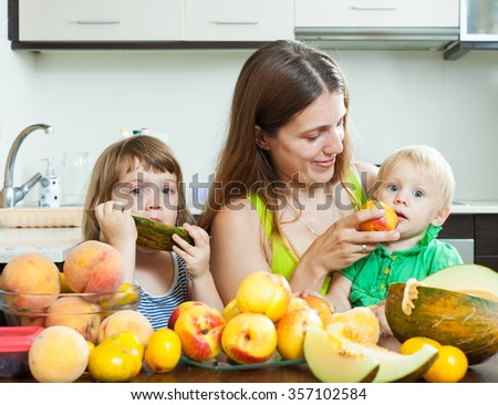 Smiling woman with children eating melon and other fruits over  table at home interior