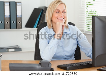 Smiling woman with chin on hand behind a desk looking at screen in an office - stock photo