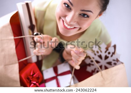 Smiling woman with christmas gifts, isolated on red - stock photo