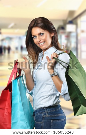 Smiling woman with colorful shopping bags at department store