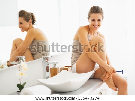 Smiling woman with disposable shaver in bathroom - stock photo